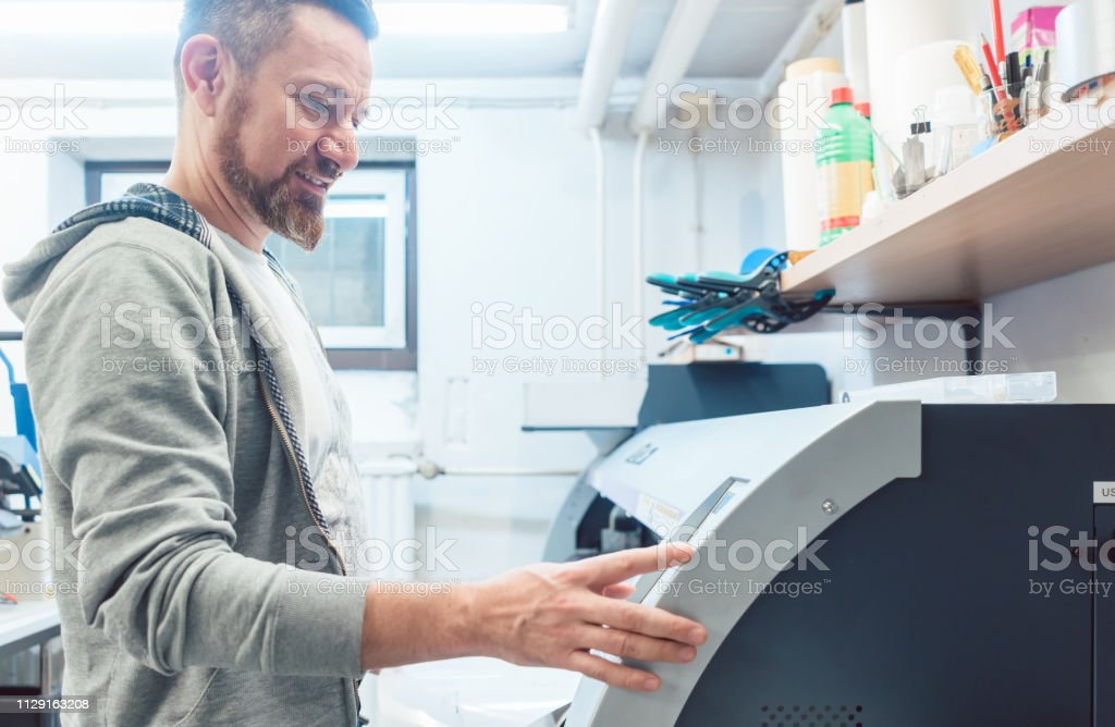 Man working on large format printer in advertising material agency...