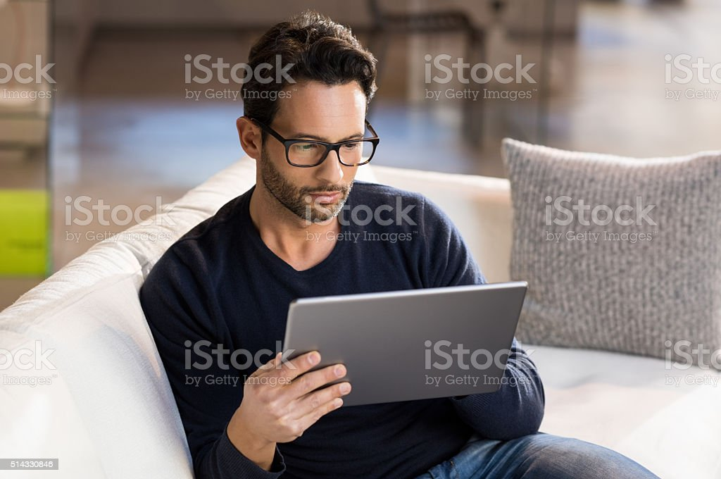 Man using digital tablet on sofa at home. Portrait of a serious man...