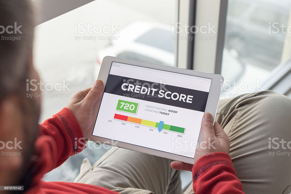 Man working on tablet with Credit Score on screen stock photo