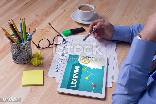 850892616 istock photo Man working on tablet with LEARNING on a screen 854320242