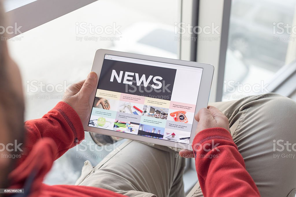 Man working on tablet with News on screen stock photo