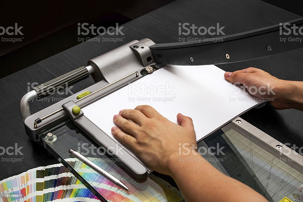 Man working on the guillotine for paper stock photo
