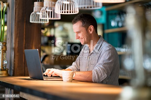 istock Man working online at a cafe 616090540