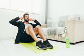 istock Man working out at home doing sit ups 1214256697