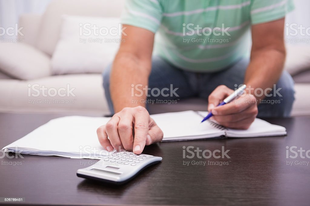 Man working out his finances on the couch stock photo