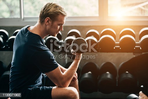 istock man working out in gym doing exercises with dumbbells. Pretty young man training in the gym 1133071902