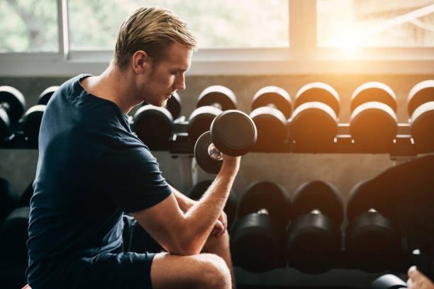 ダンベルでエクササイズをしているジムで働く男。ジムでかなり若い男の訓練 - 筋肉 ストックフォトと画像