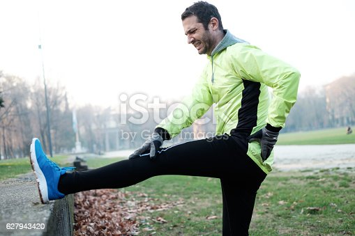 istock Man working out in the city park and stretching muscles 627943420