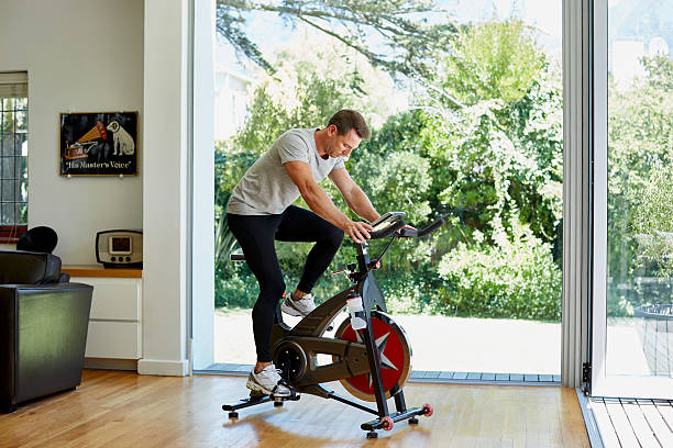 Man working out on exercise bike at home Full length of man working out on exercise bike at home exercise machine stock pictures, royalty-free photos & images