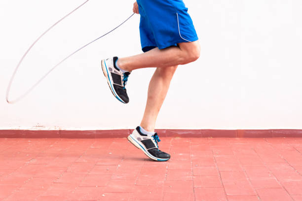 Man working out with a skipping rope on the terrace of his house stock photo