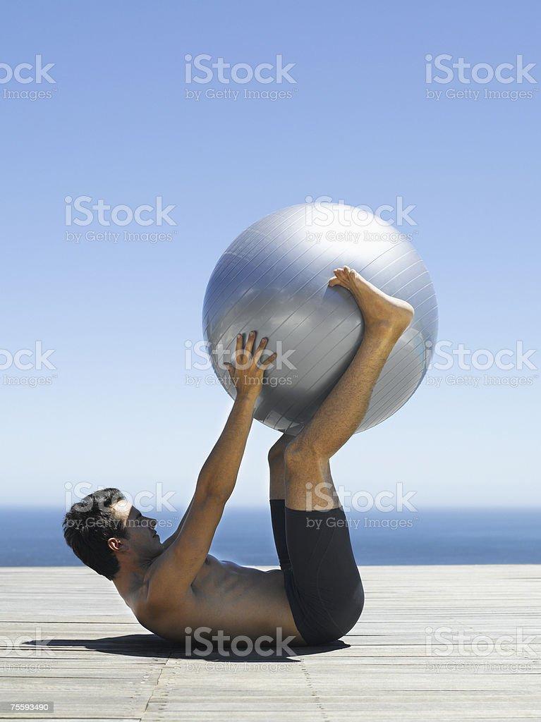 Homem a trabalhar fora com uma bola de exercício foto de stock royalty-free