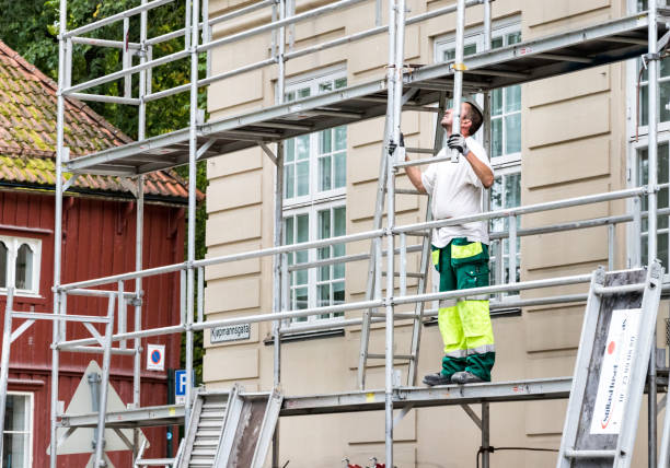 a man working standing on a scaffolding in the city center of trondheim. - fall prevention stock photos and pictures