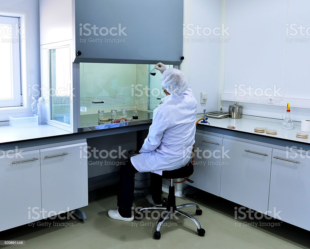 Man working under a fume hood stock photo