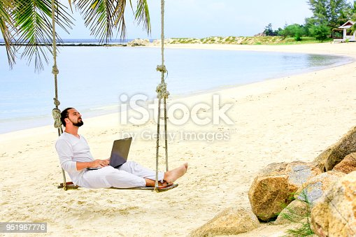 Man working with a laptop, on a hammock in the beach. Concept of digital nomad, remote worker, independent location entrepreneur. Show win