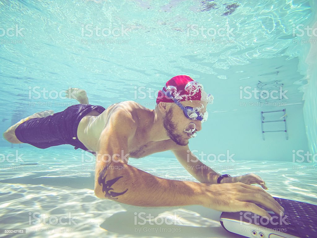 Man working with a laptop underwater stock photo
