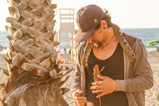 January 14, 2020 - La Serena - Coquimbo, Chile: A Man at the walking pathway with his pet lizard on his chest and a snake around his neck looking for local and tourists to take the experiences and take photos with them for a money tip.