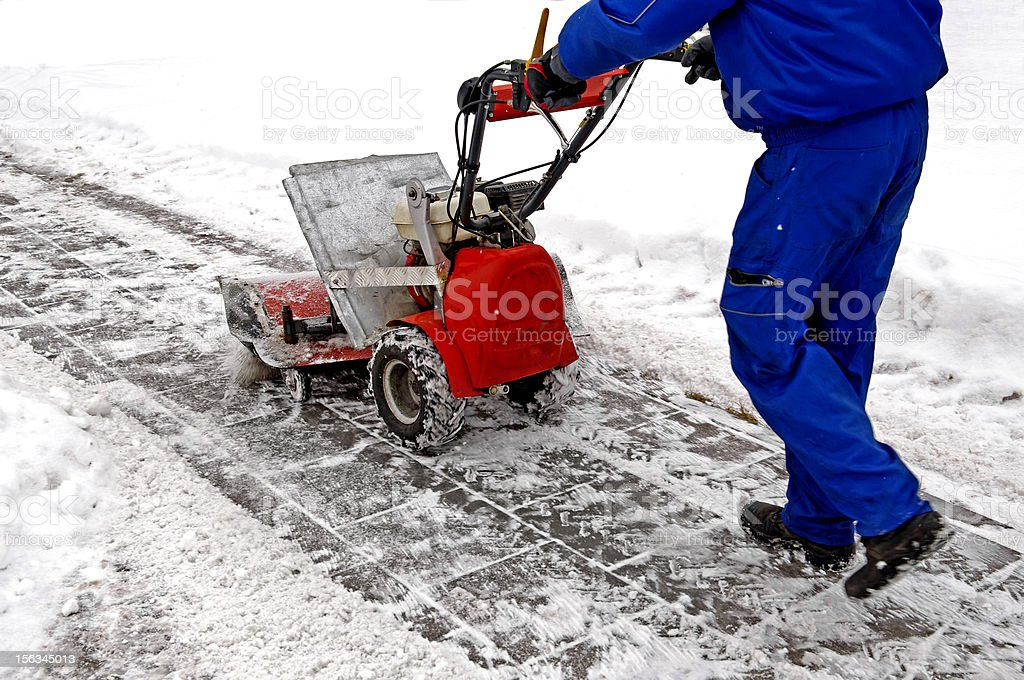 Man working with a snow blowing machine stock photo
