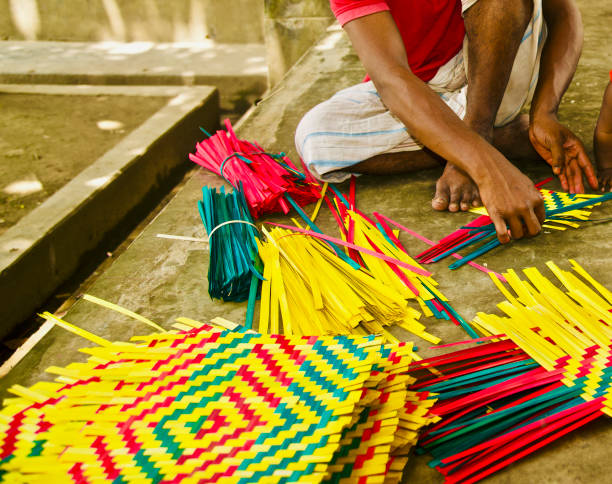 Man working with colourful bamboo objects stock photo