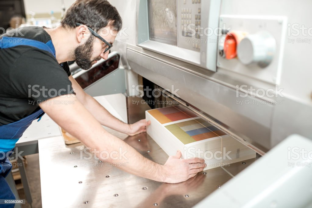 Man working with cutting machine at the printing plant stock photo