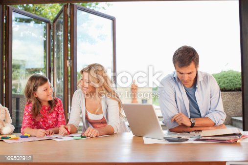 istock Man working with family in background 169502912
