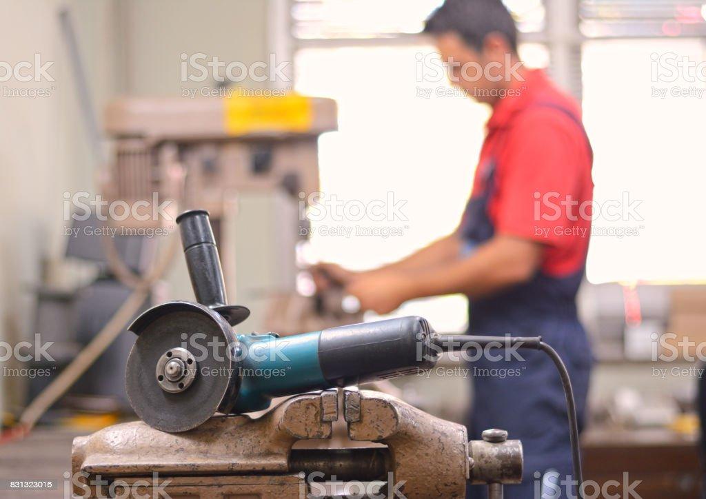 Hombre trabajo con amoladora y taladro en taller - foto de stock