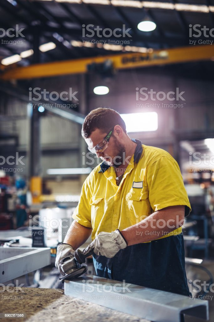 Man working with grinder in Australian manufacturing company stock photo