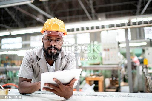 Man working with his digital tablet in the factory
