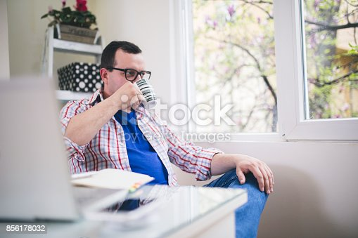 istock Man working with laptop and drinking coffee 856178032