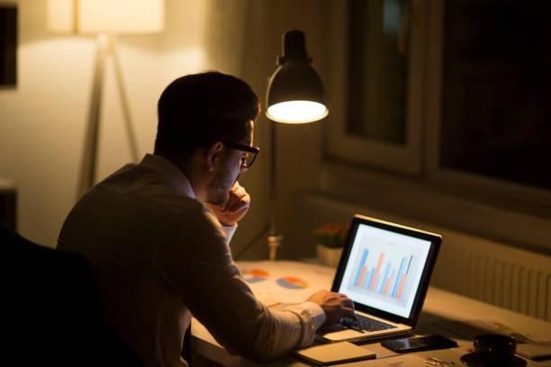 hombre que trabaja con el portátil por la noche en casa - trabajar hasta tarde fotografías e imágenes de stock