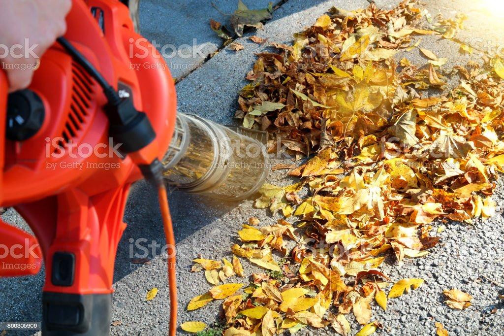 Mann, der arbeitet mit Laubbläser: die Blätter sind oben und unten verwirbelt wird, an einem sonnigen Tag – Foto