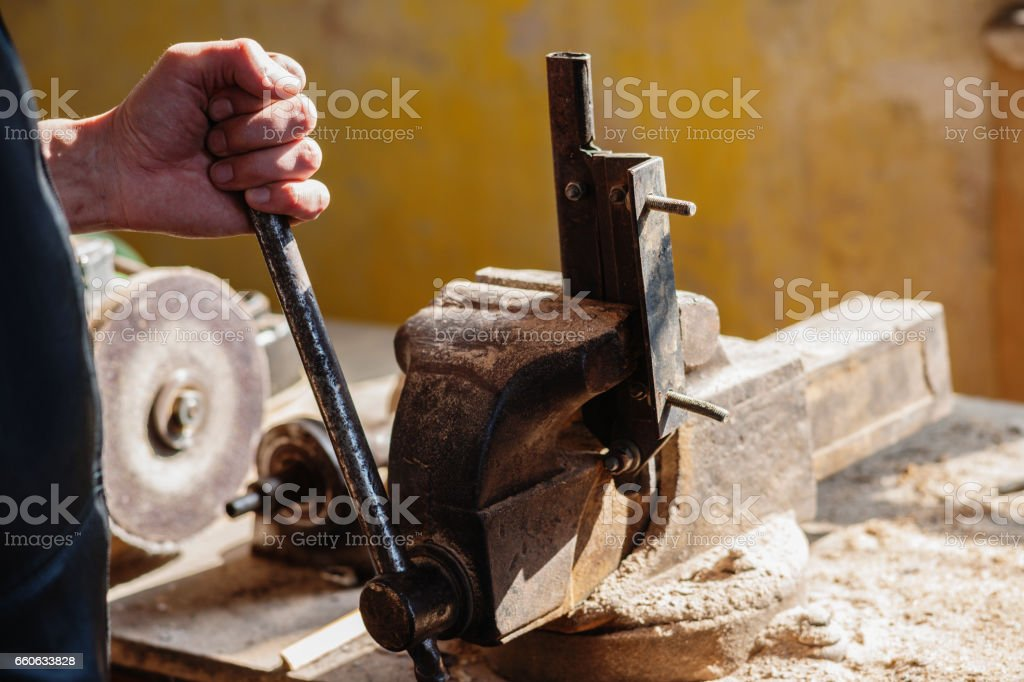 Man working with metal vise stock photo