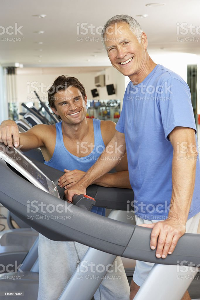 Man Working With Personal Trainer On Running Machine stock photo