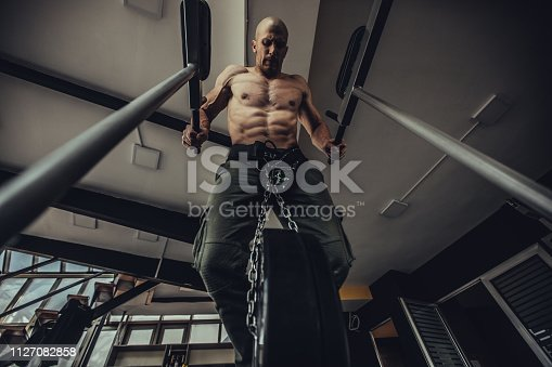 Young man exercise on exercise-machine in gym