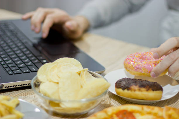A man works at a computer and eats fast food. unhealthy food: Burger, sauce, potatoes, donuts,chips. stock photo