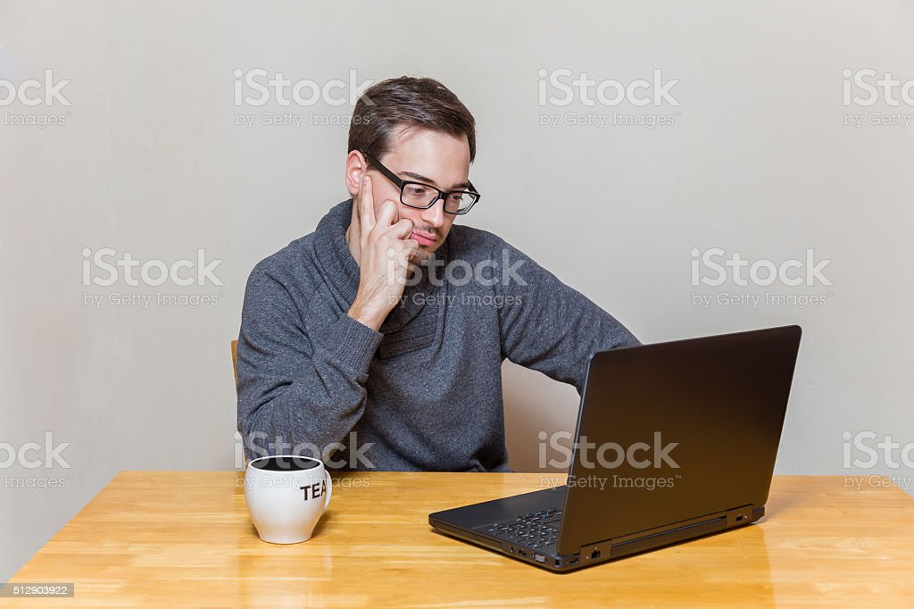 Man works bored on a laptop stock photo