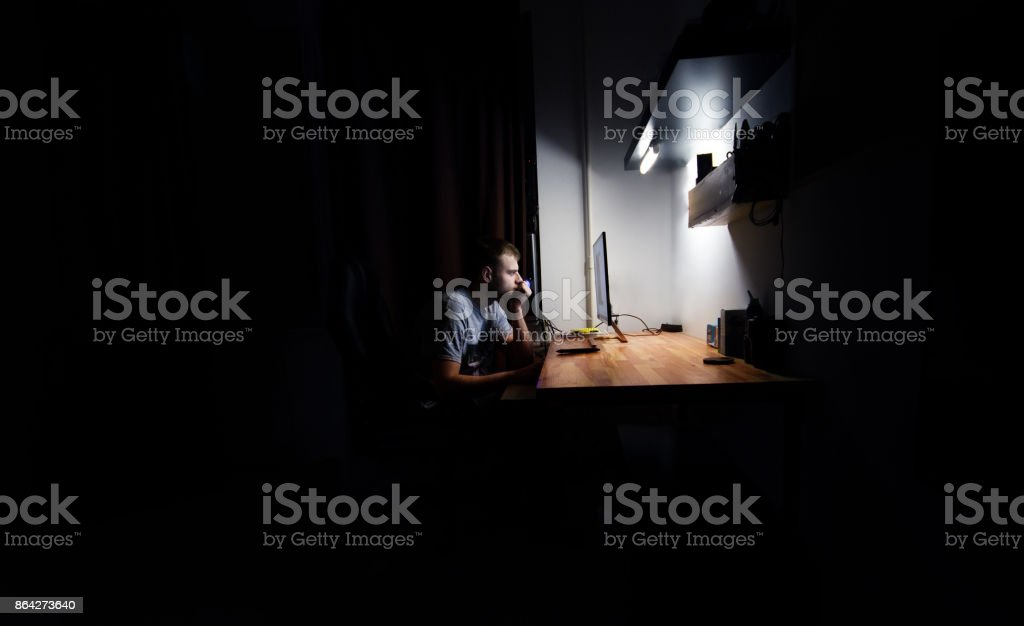 man works, resting at night at the computer in the room at home,  in the dark royalty-free stock photo
