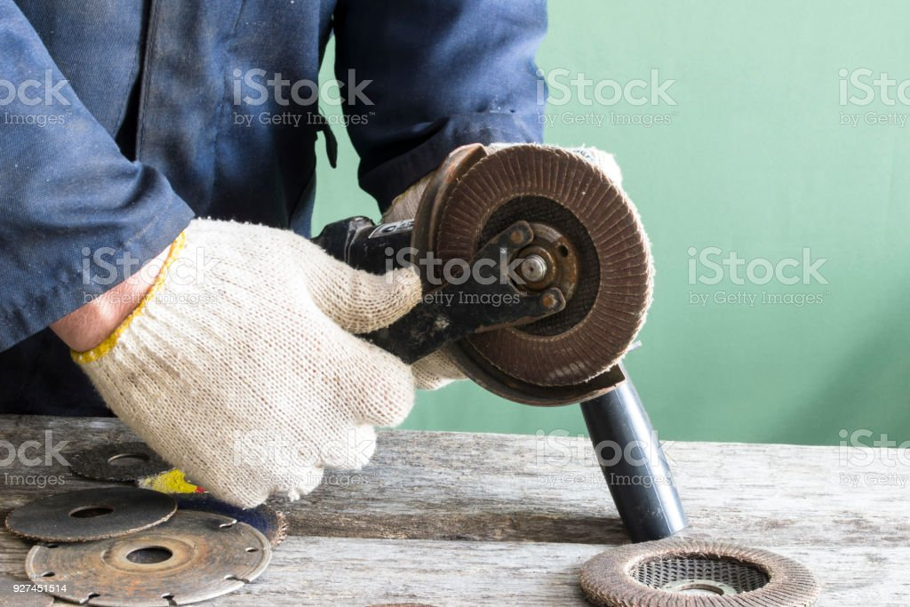 A man works with a grinding machine. stock photo