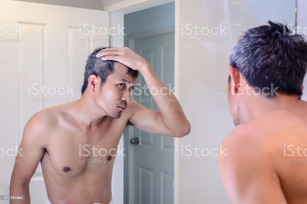 Man worried about gray hair while looking into a mirror. stock photo