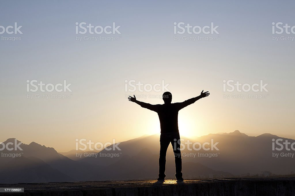 Man Worshipping at Sunrise stock photo
