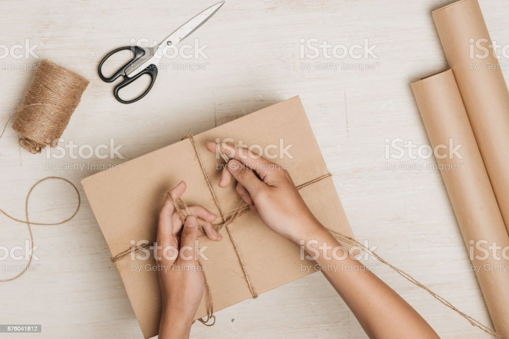Man wrapping gift. A parcel wrapped in brown paper and tied with rough twine stock photo