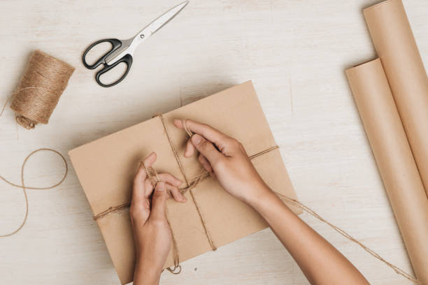 mann verpackung geschenk. ein flurstück in packpapier eingewickelt und mit groben schnur gebunden - versandrolle stock-fotos und bilder