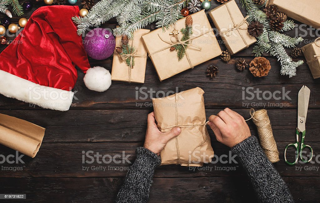 Man wraps Christmas gift on wooden table – Foto