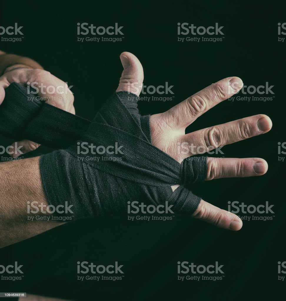 man wraps his hands in black textile bandage for sports, close up