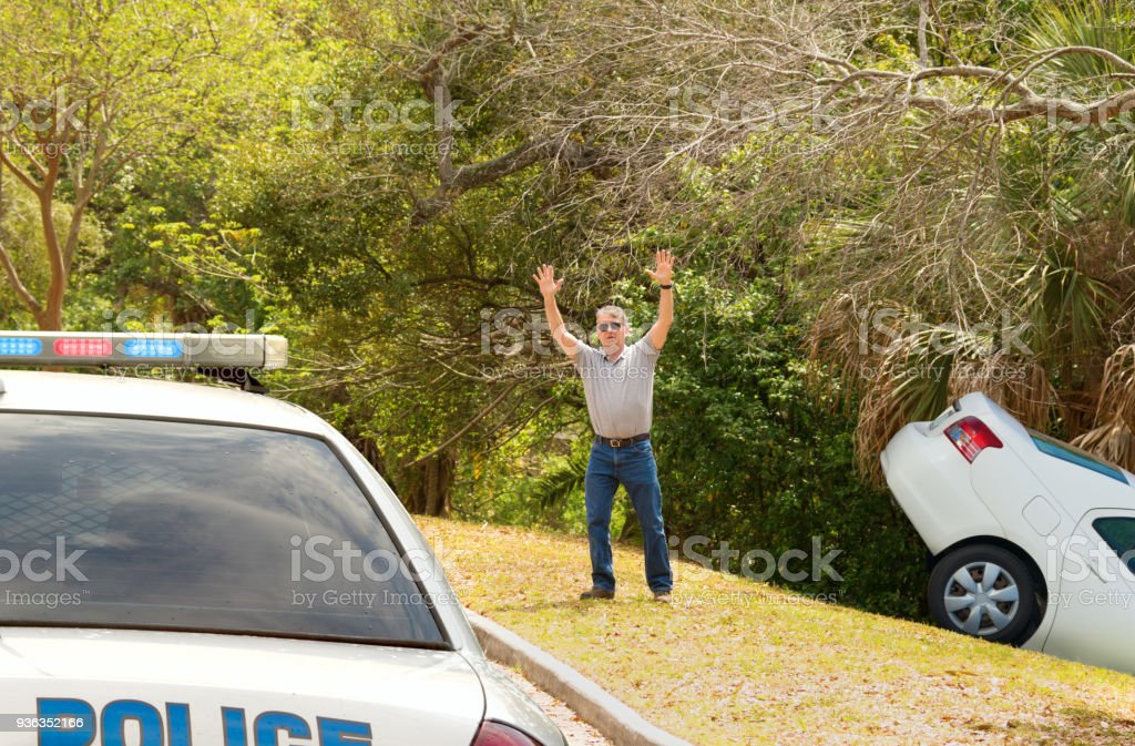 Man wrecked car into deep ditch waving down police officer car stock photo