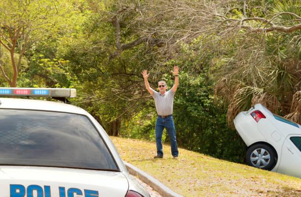 homme fait naufrage voiture dans le fossé profond agitant le policier voiture - homme faire coucou voiture photos et images de collection