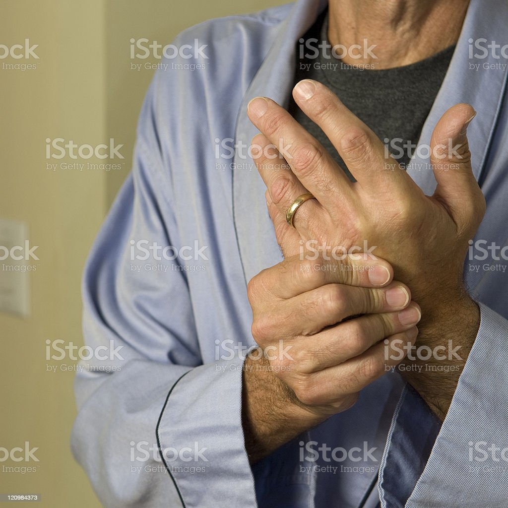 man wringing hands in pain stock photo