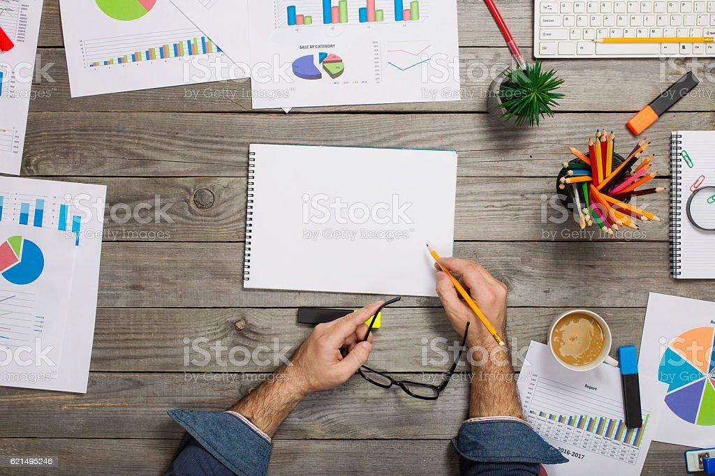 Man writes in notebook on wooden office desktop photo libre de droits