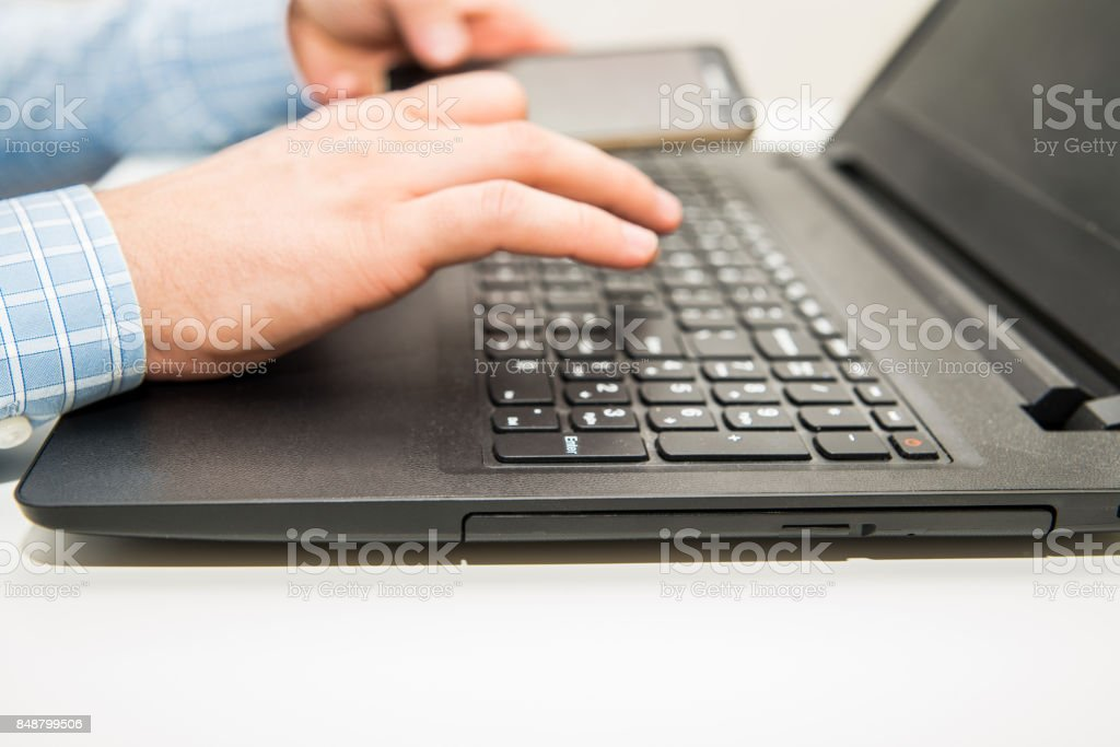 Man sitting in front of a laptop and working on a computer in his...