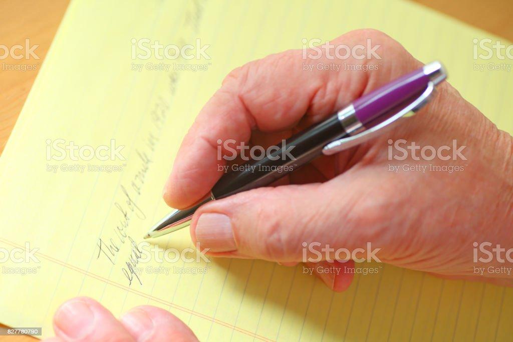 Man writes on yellow pad stock photo