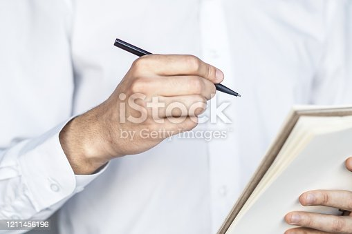 istock Man writes standing with a pen in notebook in a sunny office, business and education concept. Close up 1211456196
